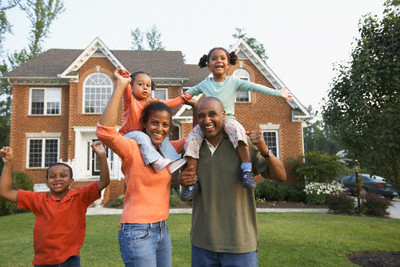 Family-Standing-in-Front-of-Home